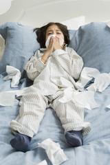 Sick Hispanic boy blowing nose