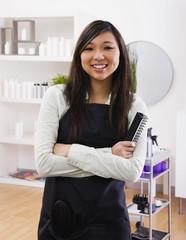Asian female hairstylist holding hairbrush