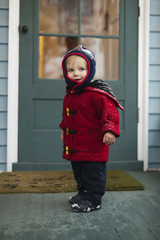 Caucasian boy wearing winter coat on porch