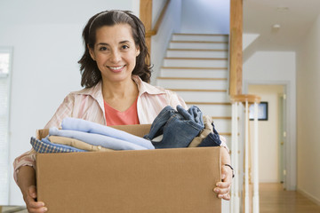Hispanic woman with box of clothing