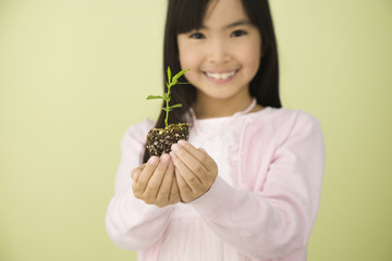 Asian girl holding new plant