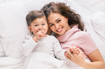 Mother playing with son on the bed