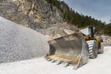 huge shovel of wheel loader at stone quarry with gravel hill - 82160379