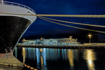 Bow of a Large Ship and Docking Ropes at Night