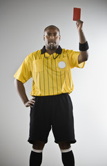 African male referee holding red card