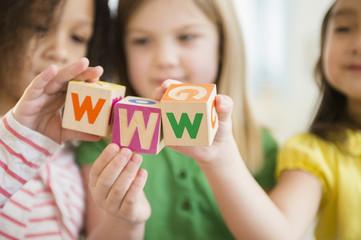 Girls holding colorful 'w' blocks