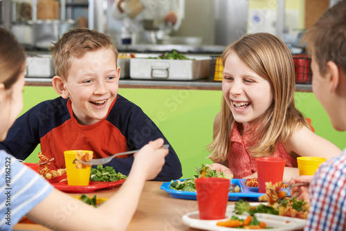 Group Of Pupils Sitting At Table In School Cafeteria Eating Meal - 82162522