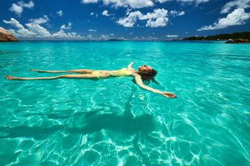 Woman in yellow bikini lying on water