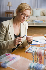 Hispanic woman making jewelry