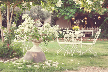 White table and chairs in beautiful garden. Vintage style