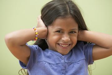 Hispanic girl covering her ears