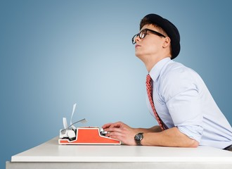 Writer. Young funny man in glasses writing on typewriter