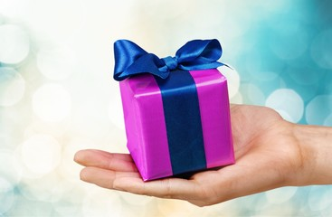 Gift. Small gift box in woman hand - christmas present, isolated