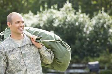 Caucasian soldier carrying duffel bag outdoors