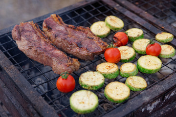 Meat and zucchini slices on grill