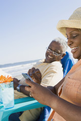 African couple looking at electronic organizer at beach