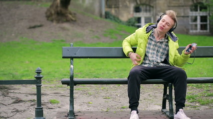 Young boy listening music and having fun in the park