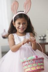 Hispanic girl in bunny ears with Easter basket