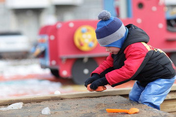 Child playing with toy in the sandbox