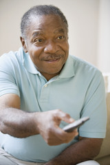 Senior African man pointing remote control