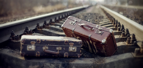 Two vintage suitcases lie on railway rails.