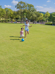 芝生広場でボール遊びする姉妹