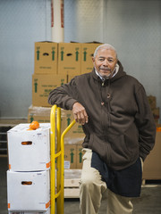 African American worker carting boxes in walk-in freezer