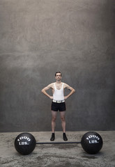 Skinny Caucasian weight lifter standing by weights