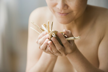 Nude Asian woman smelling dried herbs