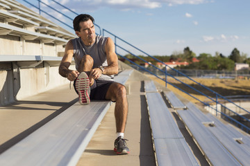 Hispanic athlete resting on bleachers
