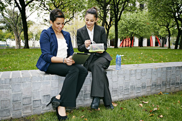 Businesswomen using tablet computer outdoors