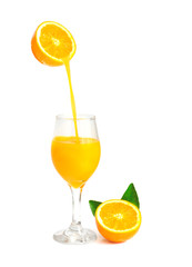 orange juice pouring into glass with orange slice and leaf, isol