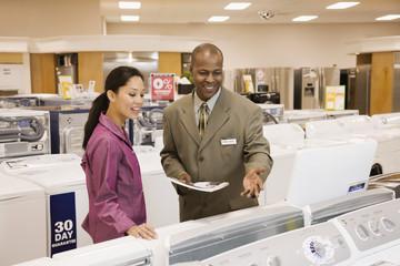 Salesman helping customer in appliance showroom