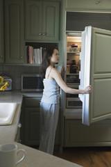 Woman opening refrigerator door