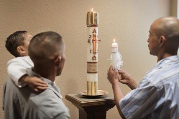 Men lighting baptismal candle in church