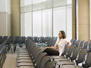 Hispanic businesswoman waiting in empty conference room