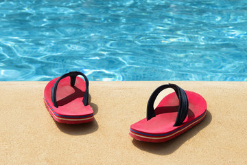 A pair of red flip flops at the swimming pool