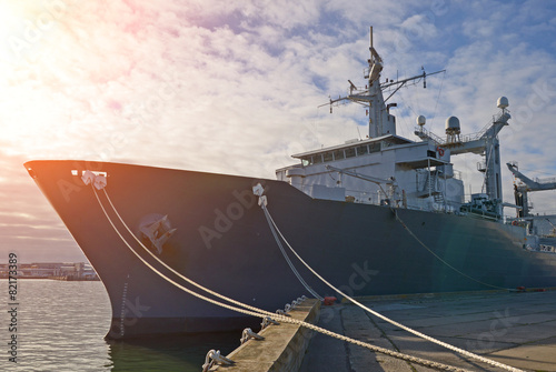 Naval auxiliary ship docked at the harbor. - 82173389