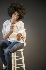 Mixed race woman doing poetry reading on stage