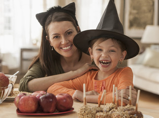 Caucasian mother and daughter wearing Halloween hats