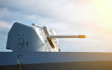 Gun on naval ship over blue sky.