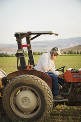 Caucasian farmer using cell phone on tractor in crop field