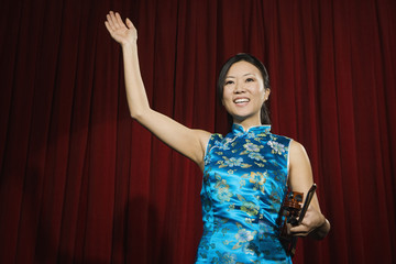 Asian woman holding violin on stage