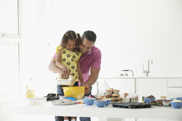 Mixed race father and daughter baking together