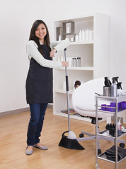 Asian female hairstylist holding broom
