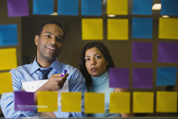 Multi-ethnic business people reviewing sticky notes