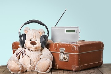 Abandoned. Retro toy Teddy Bear and radio recorder on suitcase