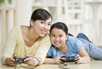 Asian mother and daughter playing video game