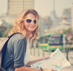 young woman with a city map and a backpack