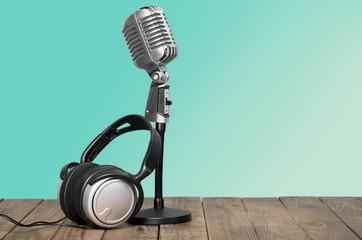 Aquamarine. Retro microphone and headphones on table